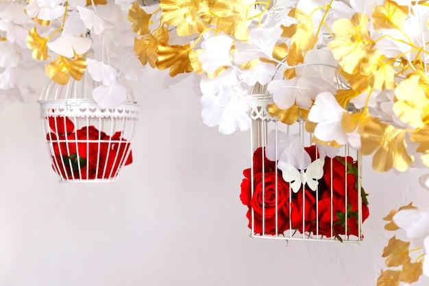 Ozdobne klatki dla ptaków na tle białej ściany z czerwonymi różami. niesamowity wystrój ślubny we wnętrzu. kwiaty w klatce do dekoracji pokoju lub przedpokoju na walentynki. tekst lub logo na stronie. skopiuj miejsce