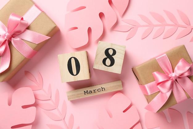 Ozdobne liście palmowe, prezenty i kalendarz na różowo, widok z góry