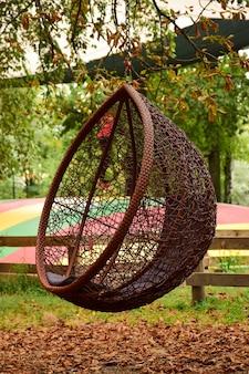 Ozdobne miejsce odpoczynku w postaci wiklinowej huśtawki zawieszonej na drzewie w jesiennym parku