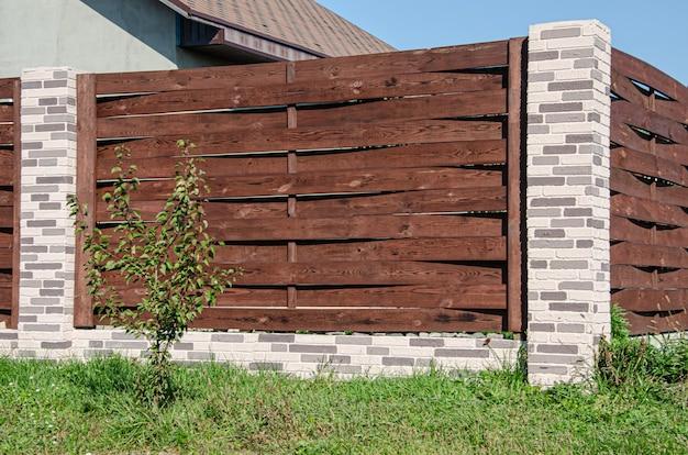 Ozdobne ogrodzenie betonowe ze słupkami ceglanymi przy budynku mieszkalnym z ogrodem.