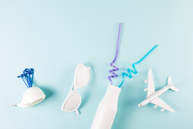 Ozdobne okulary w pobliżu samolotu zabawki z wielorybów i butelki ze słomkami