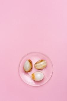 Ozdobne pisanki z kamienia na przezroczystym talerzu. trzy jajka z onyksu. koncepcja wakacji wielkanocnych.