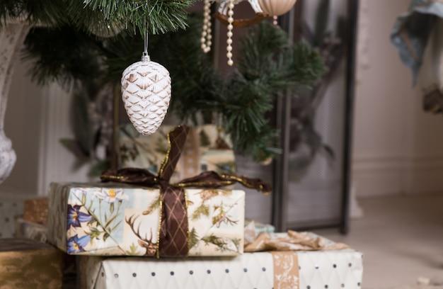 Ozdobne prezenty świąteczne ułożone u stóp choinki, aby uczcić okres świąteczny