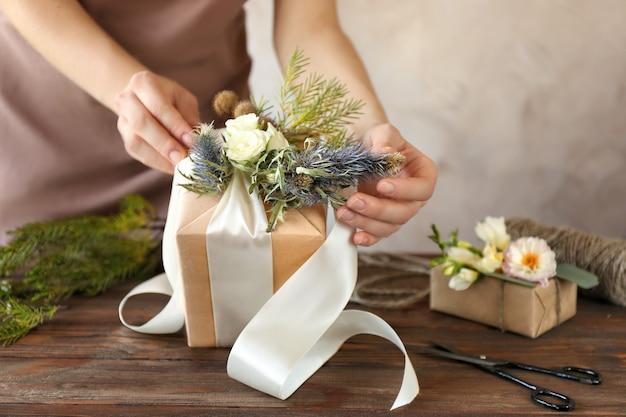 Ozdobne pudełko kwiaciarni z kwiatami i wstążką, zbliżenie
