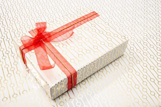 Ozdobne pudełko z czerwoną kokardą i długą wstążką. obecna koncepcja