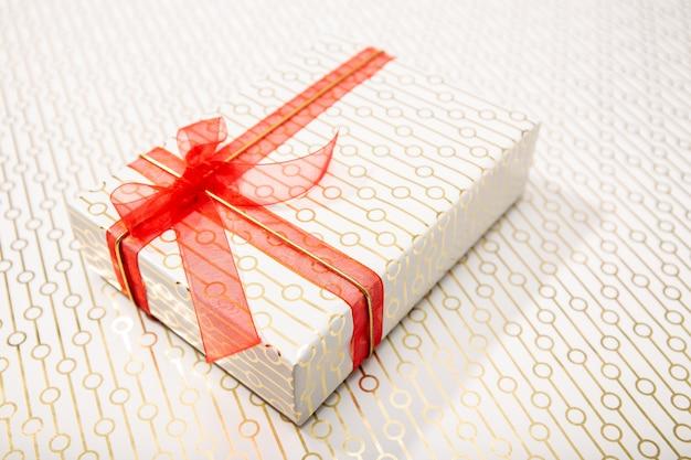 Ozdobne pudełko z czerwoną kokardą i długą wstążką