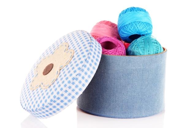 Ozdobne pudełko z kolorową przędzą na drutach na białym tle