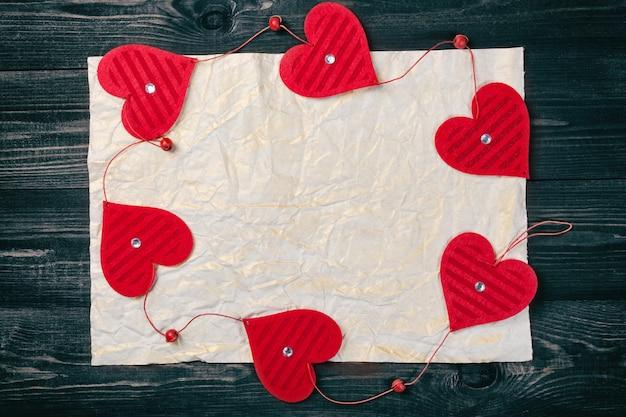 Ozdobne ramki czerwone serca na starym zmięty papier.