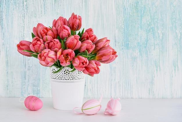 Ozdobne różowe pisanki i różowe tulipany w białym wazonie. skopiuj miejsce