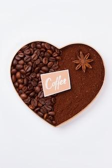 Ozdobne serce w kształcie serca wykonane z ziaren kawy. na białym tle na białej powierzchni