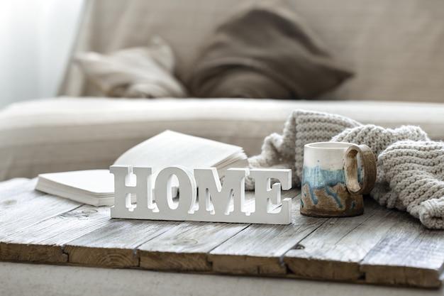 Ozdobne słowo home, filiżanka, książka i element z dzianiny we wnętrzu pokoju.