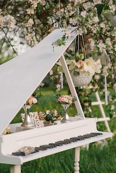 Ozdobny fortepian z wystrojem w kwitnącym sadzie jabłkowym na weselu