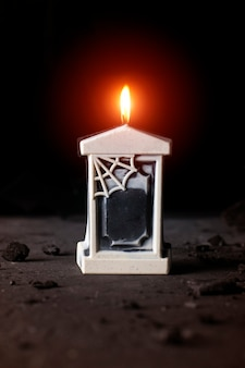 Ozdobny nagrobek świeca horror na czarnym tle.