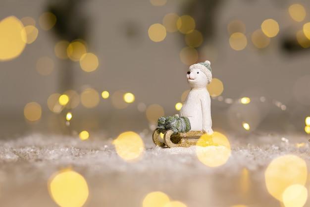 Ozdobny niedźwiedź polarny siedzi na drewnianych saniach, w czapce z dzianiny i figurkach skarpet.