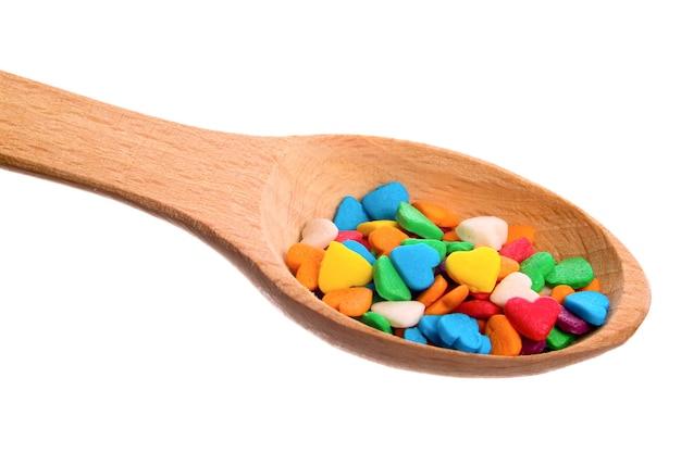 Ozdobny posypuje cukrem drewnianą łyżką na białym tle