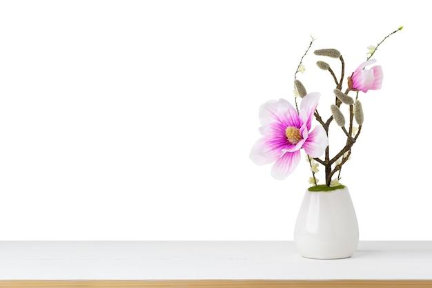 Ozdobny różowy kwiat w wazonie na stole na białym tle