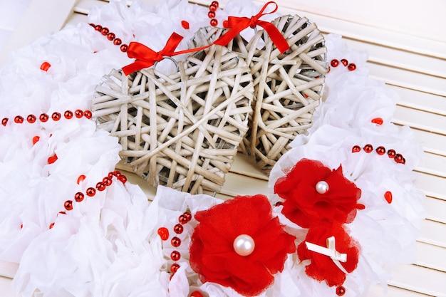 Ozdobny wieniec z wiklinowymi sercami na drewnianym tle