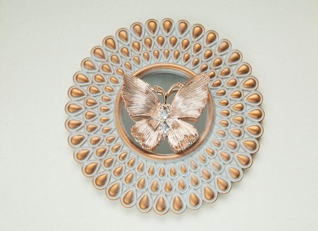 Ozdobny złoty motyl leży na okrągłym lustrze