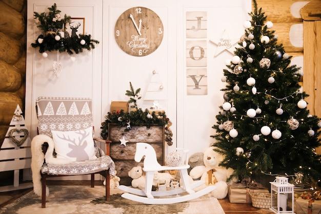Ozdoby choinkowe: krzesło, choinka, komoda, zegar, prezenty na tle drewnianej ściany. christmas photo zone. strefa zdjęć świątecznych z choinką.