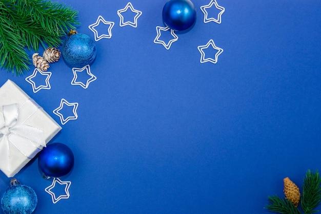 Ozdoby choinkowe kulki, szyszki, gwiazdy, pudełka na prezenty i gałęzie jodły na niebieskim tle