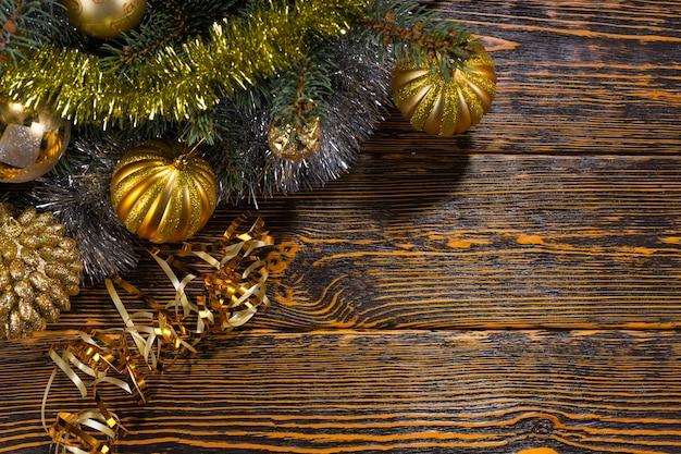 Ozdoby choinkowe o tematyce złotej z bukietem złotych bombek ułożonych na gałęzi sosny z blichtrem, układ narożny na rustykalnym drewnianym tle z copyspace
