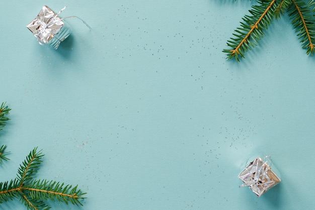 Ozdoby choinkowe w postaci pudełek prezentowych i świerkowych gałęzi na niebieskiej ścianie poziomo z kopią przestrzeni. kartkę z życzeniami boże narodzenie i nowy rok. minimalistyczny styl i design