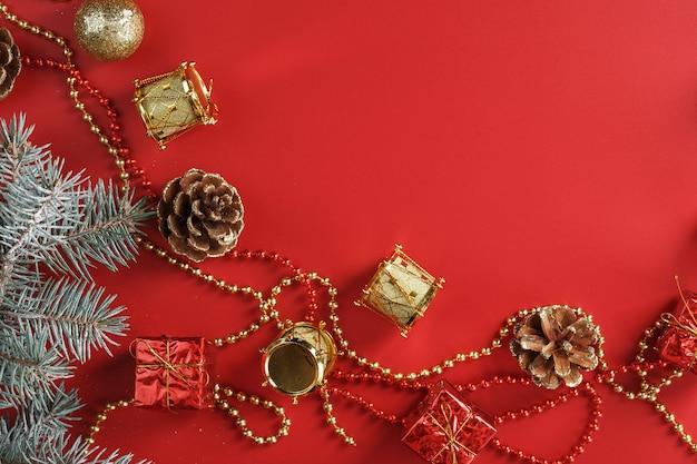 Ozdoby choinkowe z gałązkami świerkowymi na czerwonym stole z wolną przestrzenią. święta nowego roku i boże narodzenie