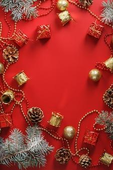 Ozdoby choinkowe z gałęzi świerkowych na czerwonym tle z wolnej przestrzeni. święta nowego roku i boże narodzenie