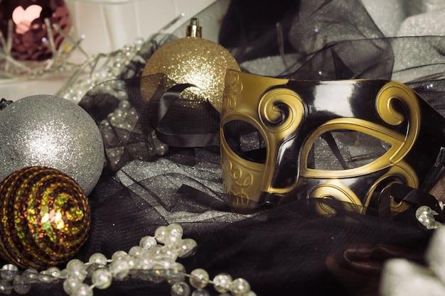 Ozdoby choinkowe z maską karnawałową na tkaninie.