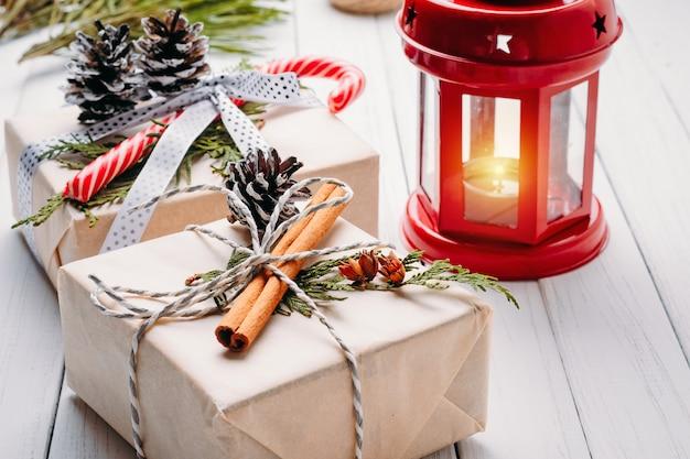 Ozdoby choinkowe z pudełka, szyszki i latarnia ze świecą na białym tle