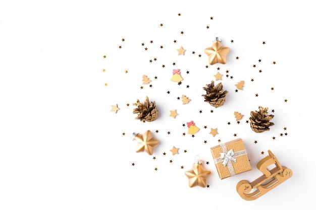 Ozdoby choinkowe ze złotymi gwiazdkami, szyszkami i prezentem na makiety na białym