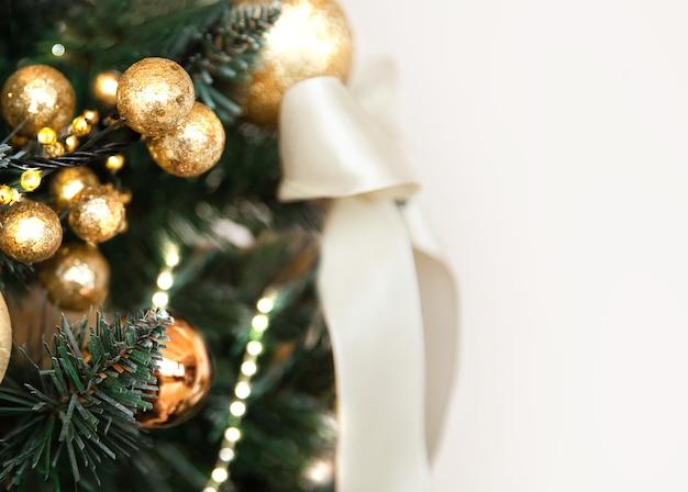 Ozdoby choinkowe złote kule i kokarda na gałęziach jodły w dużych ilościach