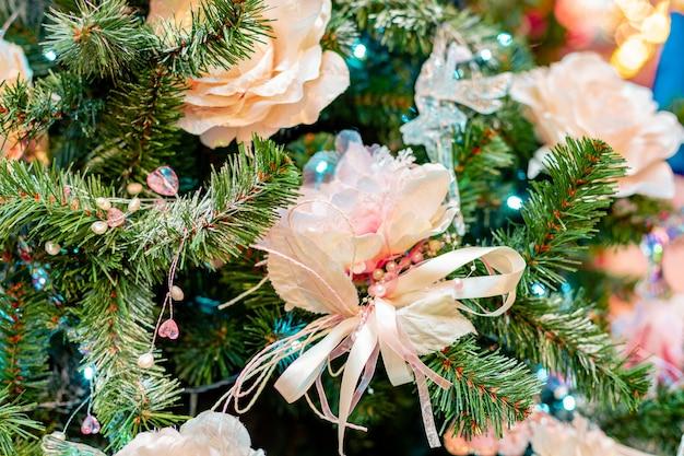 Ozdoby na choinkę. choinka z pięknymi błyszczącymi kwiatami i motylami. koncepcja ferie zimowe.