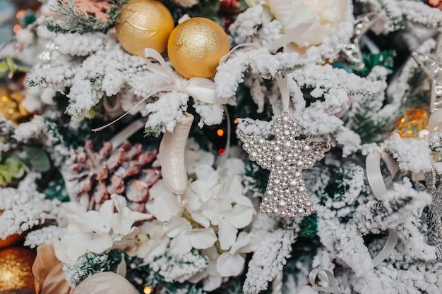 Ozdoby na choinkę. różne ozdoby świąteczne, anioły, piłki, płatki śniegu na drzewie. ozdoby świąteczne .