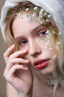 Ozdoby na głowie. niebieskooka młoda blond modelka pozuje z dekoracjami na głowie