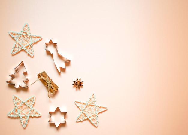 Ozdoby świąteczne: gwiazdki, zabawki, płatki śniegu. noworoczne formy na ciasteczka: choinka, gwiazdy. mieszkanie leżało na jasnym tle.