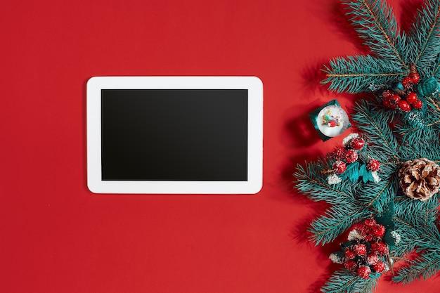 Ozdoby świąteczne i biała tabletka z czarnym ekranem na gorącym czerwonym tle. motyw bożego narodzenia i nowego roku. miejsce na twój tekst, życzenia, logo. makieta. widok z góry. skopiuj miejsce. martwa natura. leżał płasko.