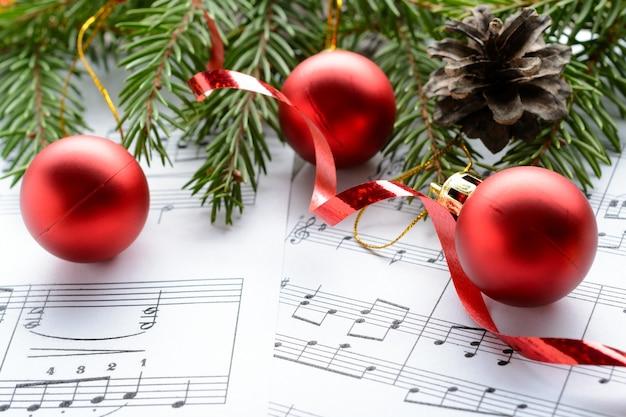 Ozdoby świąteczne i gałąź jodły leżące na arkuszu notatek