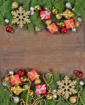 Ozdoby świąteczne i gałąź świerkowa na drewnianym tle