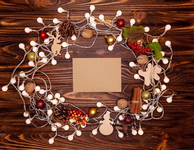 Ozdoby świąteczne i lampki choinkowe na drewnianym tle. kompozycja elementów świątecznych.
