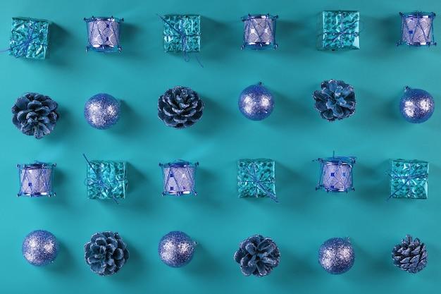 Ozdoby świąteczne i prezenty w rzędach i wzorach na niebieskiej ścianie. kompozycja świąteczna w trybie pełnoekranowym