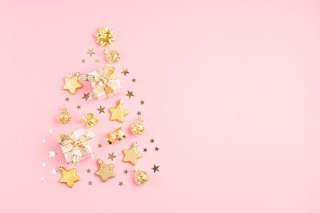 Ozdoby świąteczne i pudełka na prezenty ułożone w kształcie choinki na różowej powierzchni