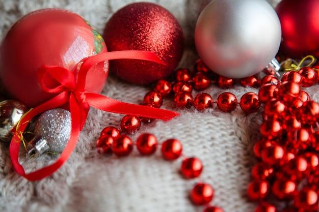Ozdoby świąteczne i świąteczny wystrój świąteczny. czerwony błyszczący asortyment ozdób. kuleczki i sznureczek na dzianinie z teksturą.