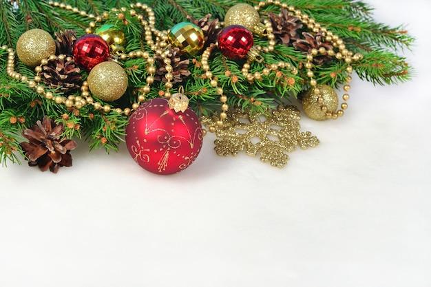 Ozdoby świąteczne i świerkowa gałąź i szyszki na białym tle