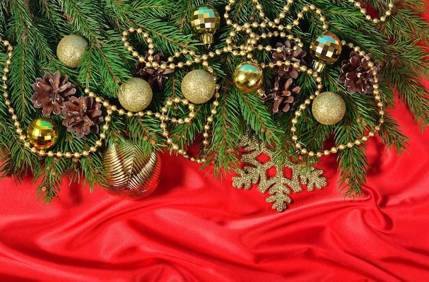 Ozdoby świąteczne i świerkowa gałąź i szyszki na czerwonym tle