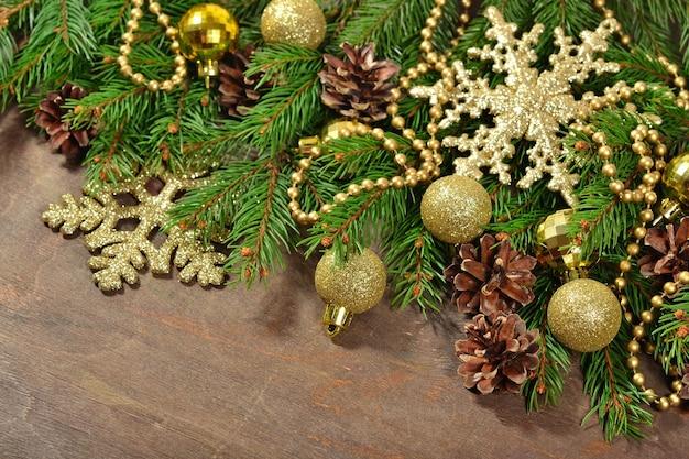 Ozdoby świąteczne i świerkowa gałąź i szyszki na drewnianym tle