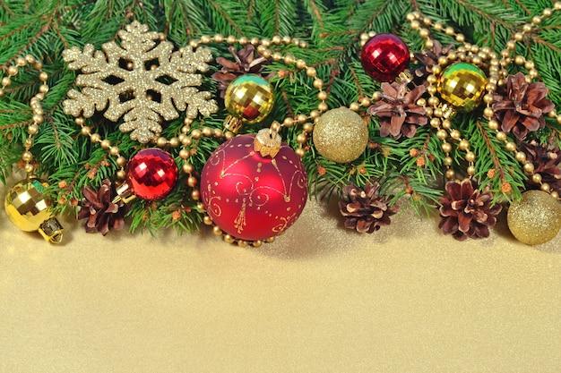 Ozdoby świąteczne i świerkowa gałąź i szyszki na złotym tle