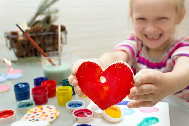 Ozdoby świąteczne. mała dziewczynka zrobiła i pomalowała serce
