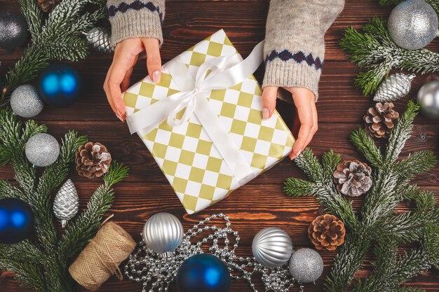Ozdoby świąteczne na drewnianym stole ze zdobionym prezentem w rękach kobiety