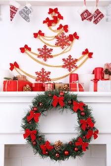 Ozdoby świąteczne na kominku na tle białej ściany